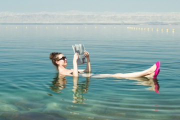 Woman in water reading newspaper